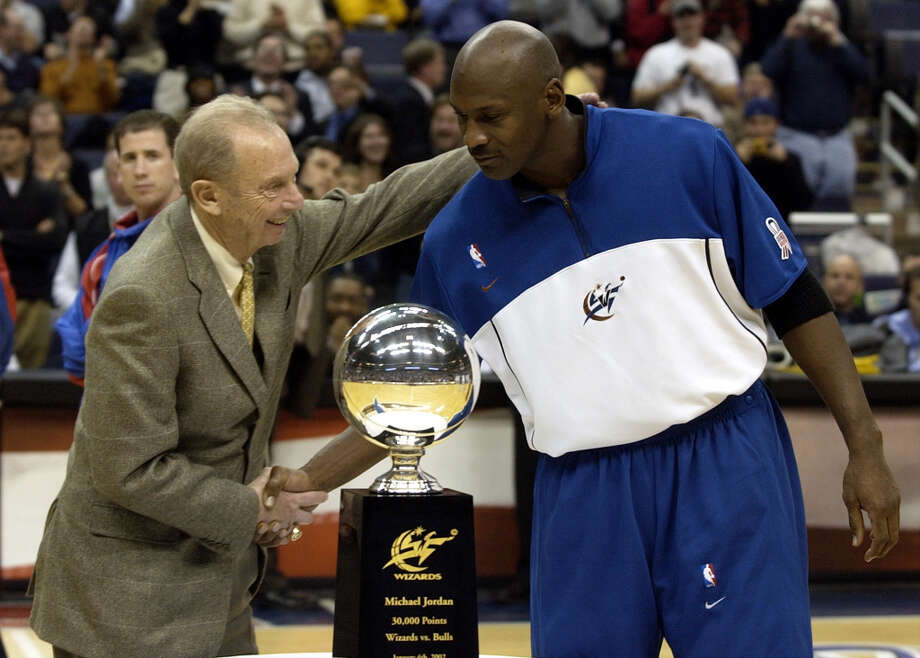 Washington Wizards' chairman of the board Abe Pollin, left, shakes hands with Wizards' Michael Jordan, right, as he presented Jordan with a trophy that commemorated his 30,000 point scoring milestone during the halftime of their game against the Los Angeles Clippers, in this Jan. 8, 2002 photo at the MCI Center in Washington. Photo: NICK WASS, AP / AP