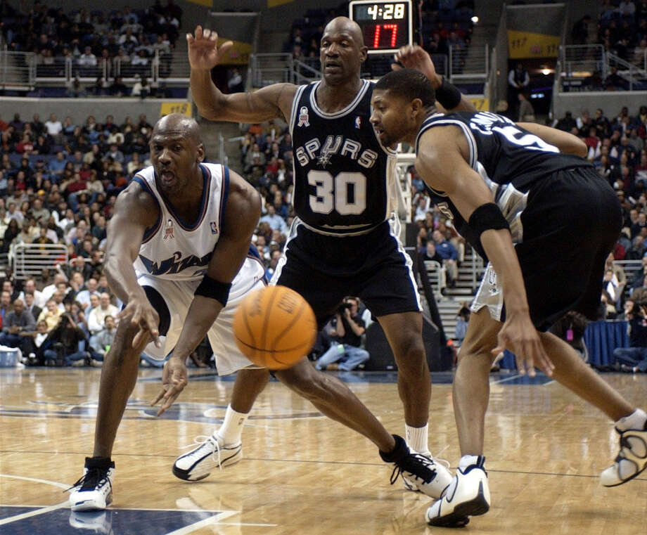 Washington Wizards' Michael Jordan, left, passes the ball against San Antonio Spurs' Terry Porter (30) and Charles Smith, right, during the second quarter, Tuesday, Jan. 15, 2002, at the MCI Center in Washington. Photo: NICK WASS, AP / AP