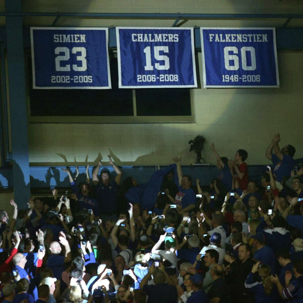 A banner with the No. 15 of former Kansas player Mario Chalmers is revealed during a ceremony retiring his college jersey during an NCAA college basketball game between Texas and Kansas, Saturday, Feb. 16, 2013, in Lawrence, Kan. (AP Photo/Ed Zurga)