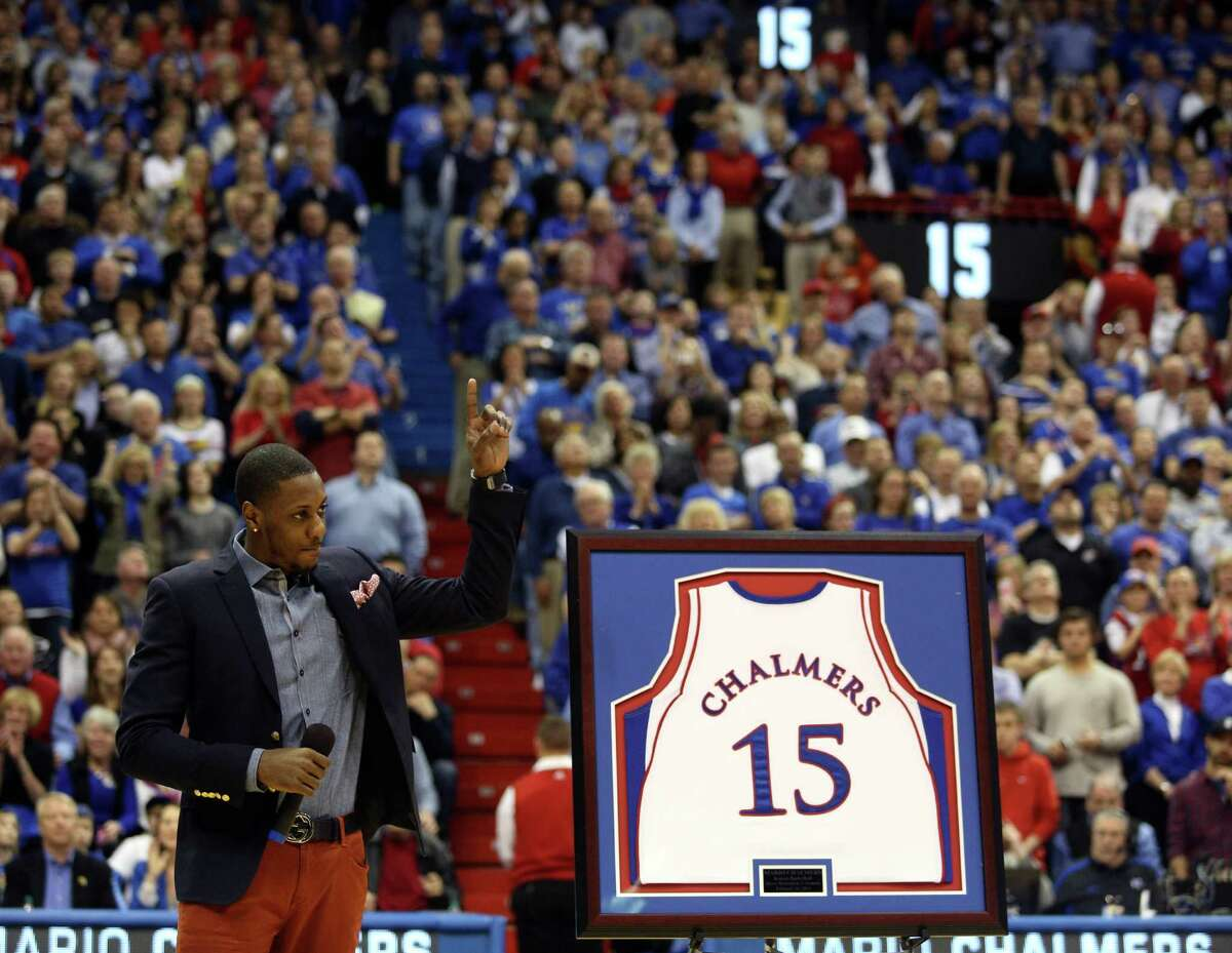 Kansas alum and Miami Heat NBA basketball player Mario Chalmers waves to the crowd as his No. 15 jersey is retired during a ceremony at halftime of an NCAA college basketball game between Texas and Kansas Saturday, Feb. 16, 2013, in Lawrence, Kan.