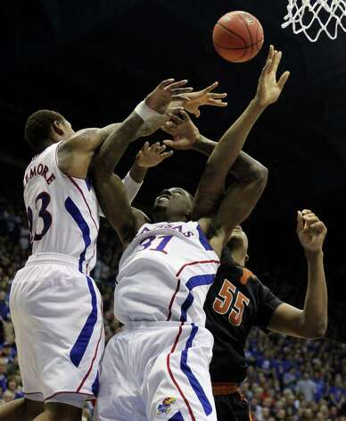 Kansas' Ben McLemore (23) and Jamari Traylor (31) battle for a rebound against Texas' Cameron Ridley (55) during the second half of an NCAA college basketball game on Saturday, Feb. 16, 2013, in Lawrence, Kan. Kansas won 73-47.  (AP Photo/Ed Zurga) Photo: Ed Zurga, Associated Press / FR34145 AP