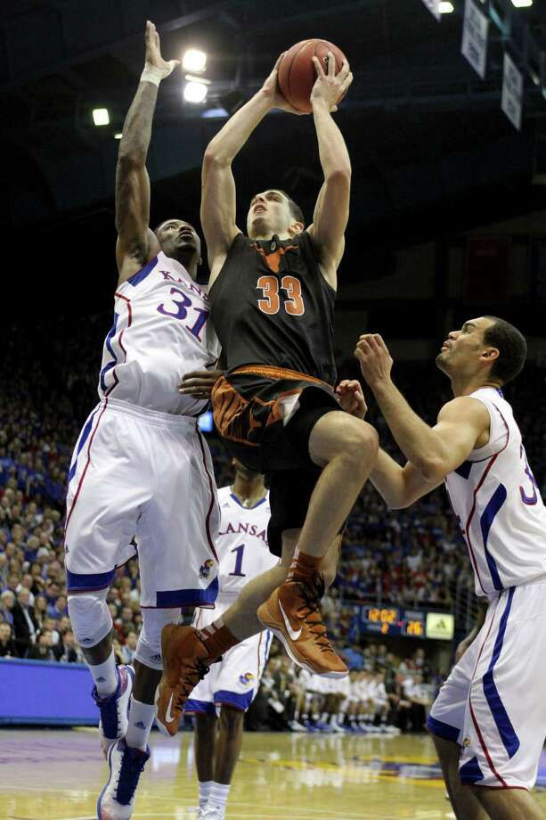 Texas' Ioannis Papapetrou (33) shoots between Kansas' Jamari Traylor (31) and Perry Ellis  during the second half of an NCAA college basketball game on Saturday, Feb. 16, 2013, in Lawrence, Kan. Kansas won 73-47. (AP Photo/Ed Zurga) Photo: Ed Zurga, Associated Press / FR34145 AP