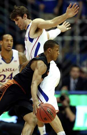 Texas guard Demarcus Holland, front, drives around Kansas center Jeff Withey during the first half of an NCAA college basketball game on Saturday, Feb. 16, 2013, in Lawrence, Kan. (AP Photo/Ed Zurga) Photo: Ed Zurga, Associated Press / FR34145 AP