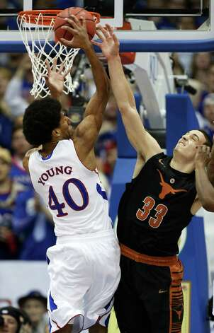 Kansas' Kevin Young (40) grabs a rebound past Texas' Ioannis Papapetrou (33) during the first half of an NCAA college basketball game on Saturday, Feb. 16, 2013, in Lawrence, Kan. (AP Photo/Ed Zurga) Photo: Ed Zurga, Associated Press / FR34145 AP