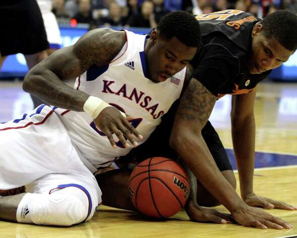 Kansas forward Jamari Traylor, left, and Texas center Cameron Ridley battle for a loose ball during the first half of an NCAA college basketball game on Saturday, Feb. 16, 2013, in Lawrence, Kan. (AP Photo/Ed Zurga) Photo: Ed Zurga, Associated Press / FR34145 AP
