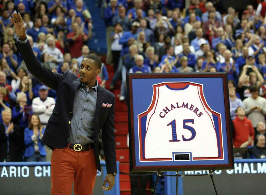Former Kansas player and current Miami Heat member Mario Chalmers waves to the crowd as his college jersey is retired during a halftime ceremony at an NCAA college basketball game between Texas and Kansas, Saturday, Feb. 16, 2013, in Lawrence, Kan. (AP Photo/Ed Zurga) Photo: Ed Zurga, Associated Press / FR34145 AP