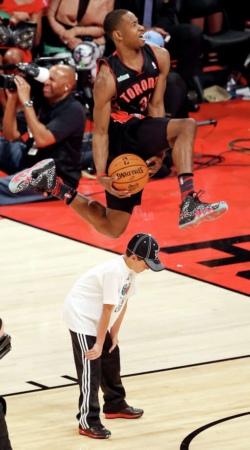 Toronto Raptors' Terrence Ross dunks over a ball boy during the Sprite Slam Dunk Contest at the Toyota Center Saturday, Feb. 16, 2013, in Houston. Ross won the competition. Photo: Edward A. Ornelas, San Antonio Express-News / © 2013 San Antonio Express-News