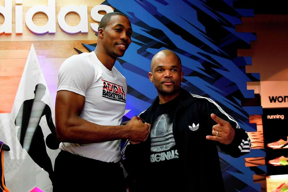 NBA All-Star Dwight Howard of the Los Angeles Lakers and hip-hop legend D.M.C. pose during a fan event Feb. 16 at the Adidas Store at Galleria Mall during NBA All-Star in Houston. (Photo by Noah Graham/NBAE via Getty Images)
