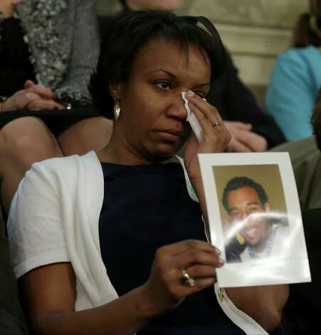 Carolyn Murray wipes her eye as she holds a photo of her son Justin during President Barack Obama' State of the Union address during a joint session of Congress on Capitol Hill in Washington, Tuesday. Murray was shot and killed in Evanston, Ill. Nov. 29, 2012. In his speech, the president called for reforms of the nation's gun laws. Photo: AP