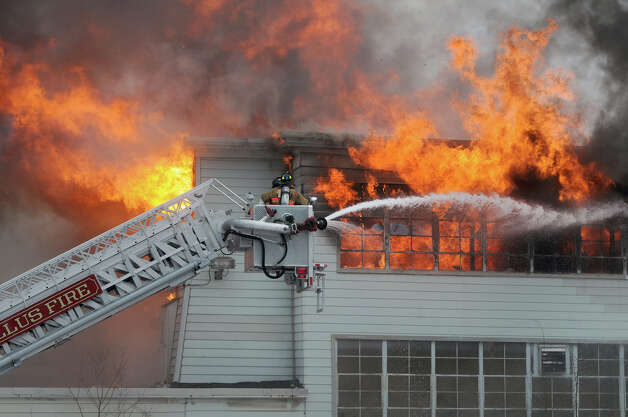 Camillus firefighters spray water from a ladder truck on the former Camillus Cutlery in Camillus Monday afternoon. Demolition and fire crews worked overnight to extinguish the fire that started at 1:20 p.m. when a portion of wall caught fire during demolition work inside. A worker escaped on his own. Firefighters continued to put out hot spots Tuesday morning. Photo: AP