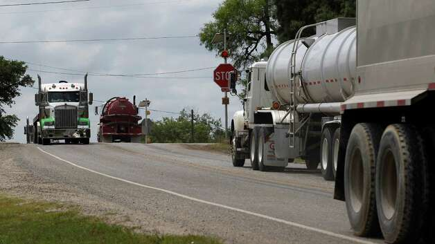 A steady stream of trucks pass through the small town of Kenedy, Texas, Wednesday, May 9, 2012. A UTSA report says South Texas's Eagle Ford Shale supported nearly 48,000 jobs last year while creating overnight boom towns cashing in on a $25 billion economic windfall. The energy rush that started in 2008 mushroomed into nearly 1,700 wells last year. (AP Photo/Eric Gay) Photo: Eric Gay, Associated Press / AP