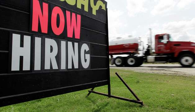 An oil truck passes a now hiring sign, Wednesday, May 9, 2012, in Kenedy, Texas. A UTSA report says South Texas's Eagle Ford Shale supported nearly 48,000 jobs last year while creating overnight boom towns cashing in on a $25 billion economic windfall. The energy rush that started in 2008 mushroomed into nearly 1,700 wells last year. (AP Photo/Eric Gay) Photo: Eric Gay, Associated Press / AP