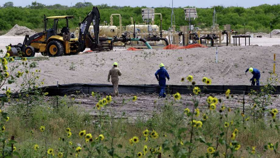 Oil workers in the Eagle Ford region are seen at a site near Karnes City, Texas, Wednesday, May 9, 2012. A UTSA report says South Texas's Eagle Ford Shale supported nearly 48,000 jobs last year while creating overnight boom towns cashing in on a $25 billion economic windfall. The energy rush that started in 2008 mushroomed into nearly 1,700 wells last year. (AP Photo/Eric Gay) Photo: Eric Gay, Associated Press / AP