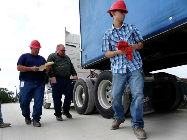 Eugene Martinez, left, Max Gasner, and Joseph Placencia go through a truck inspection exercise for drivers at Frac Tech, now called FTI International near Pleasanton on April 6 2012. The demand is high for truck drivers in the Eagle Ford shale industry. Billy Calzada / San Antonio Express-News Photo: BILLY CALZADA, San Antonio Express-News / SAN ANTONIO EXPRESS-NEWS