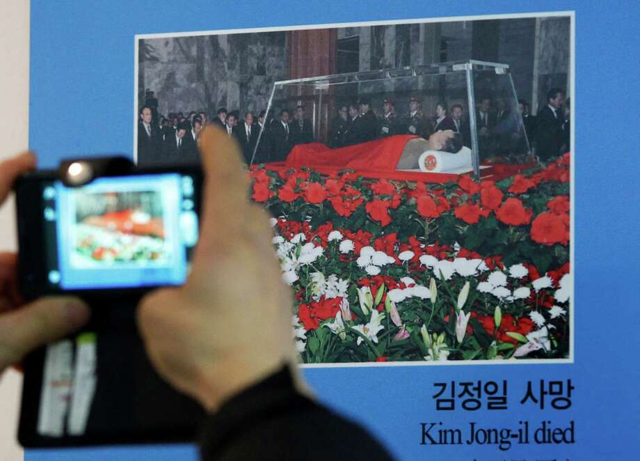 A visitor takes a picture of a photo of the body of late North Korean leader Kim Jong Il on display at a unification observation post in Paju near the demilitarized zone (DMZ) of Panmunjom, South Korea, Sunday. Photo: AP