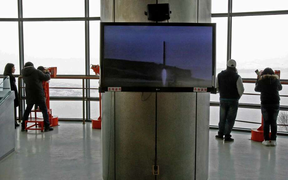 A video screen shows a 2006 file footage of the North Korean rocket Taepodong launch as visitors look over the North at a unification observation post in Paju near the demilitarized zone (DMZ) of Panmunjom, South Korea, Sunday. Photo: AP