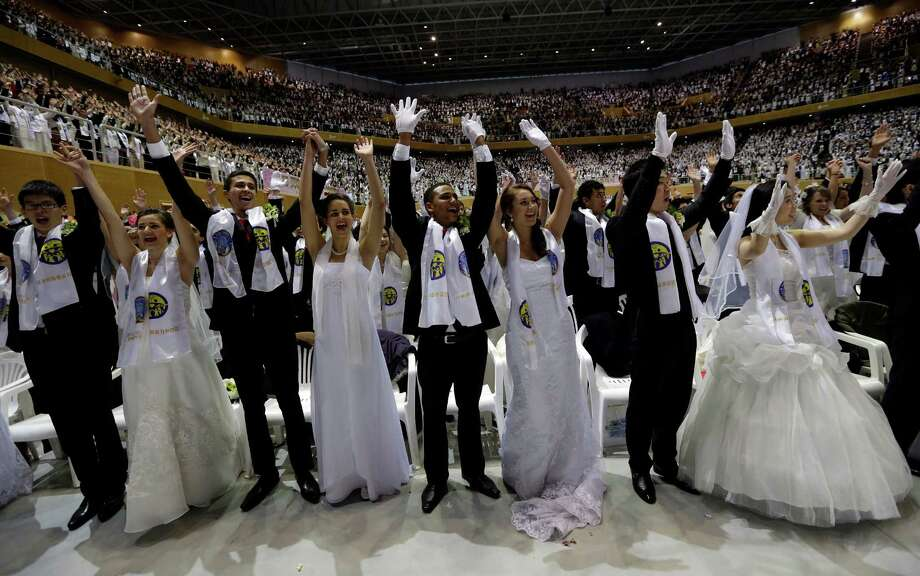 Newly-married couples from around the world cheer in a mass wedding ceremony at the CheongShim Peace World Center in Gapyeong, South Korea, Sunday. Photo: AP