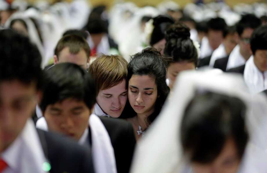 Couples from around the world pray in a mass wedding ceremony at the CheongShim Peace World Center in Gapyeong, South Korea, Sunday. Photo: AP