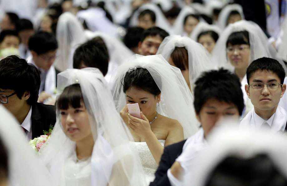 A bride checks her make up in a mass wedding ceremony at the CheongShim Peace World Center in Gapyeo