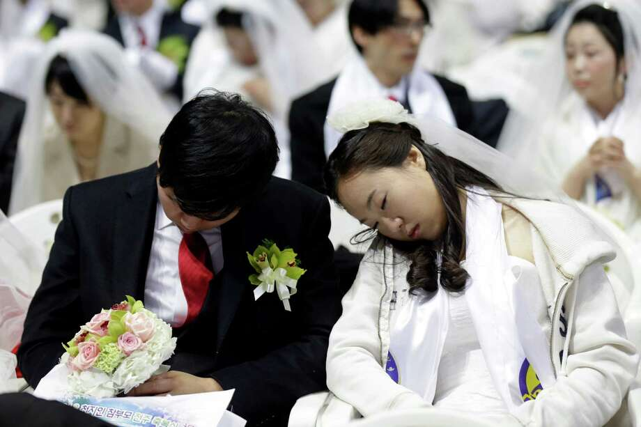 A newly-married couple takes a nap before their mass wedding ceremony at the CheongShim Peace World Center in Gapyeong, South Korea, Sunday. Photo: AP