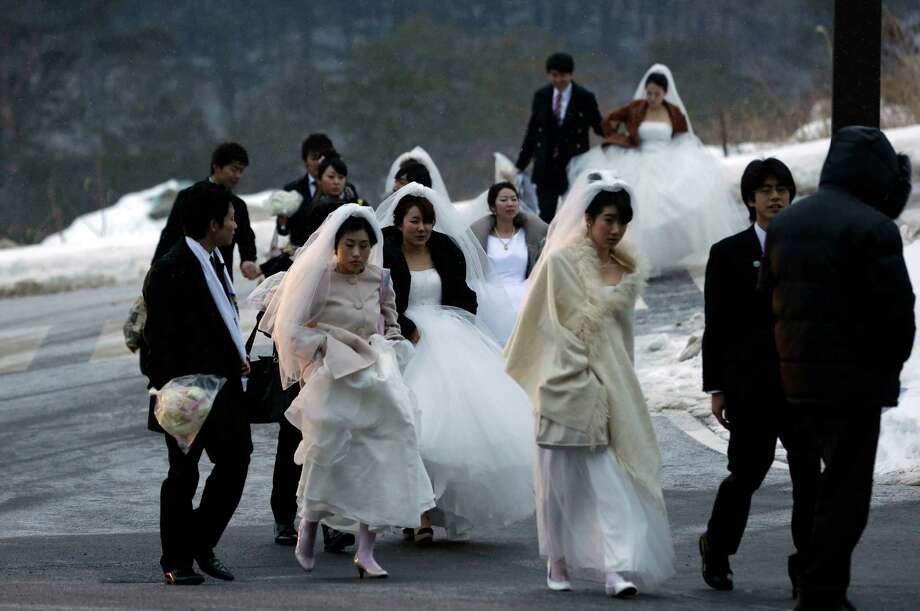 Couples arrive for their mass wedding ceremony at the CheongShim Peace World Center in Gapyeong, South Korea, Sunday. Some 3,500 South Korean and foreign couples exchanged or reaffirmed marriage vows in the Unification Church's mass wedding arranged by Hak Ja Han Moon, a wife of the late Rev. Sun Myung Moon, the controversial founder of the Unification Church. Photo: AP