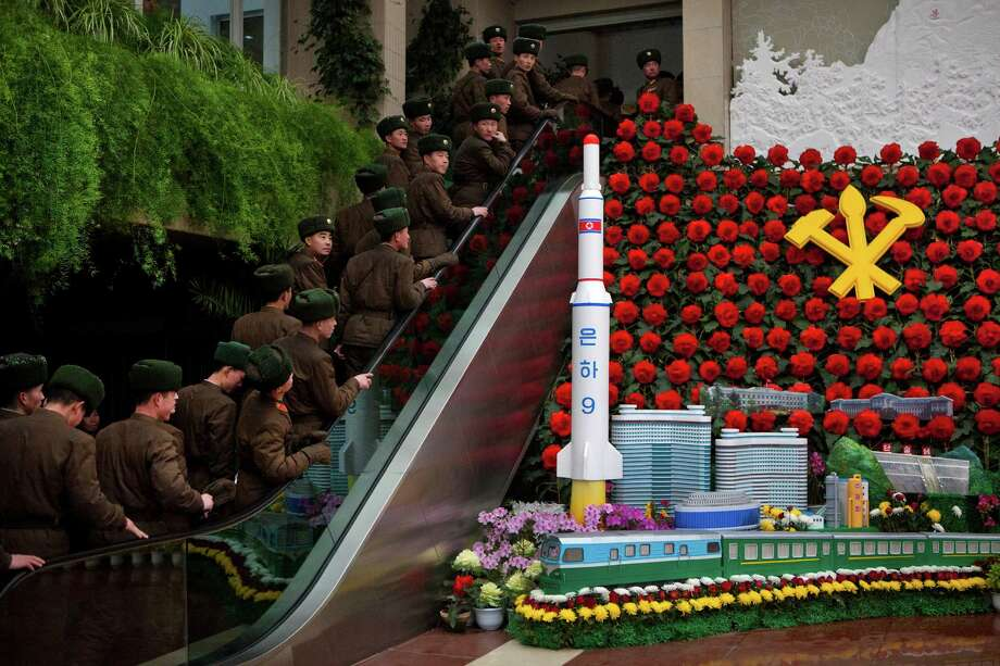 North Korean soldiers ride an escalator past a model of their country's Unha Rocket as they enter an exhibition in Pyongyang on Sunday. Photo: AP