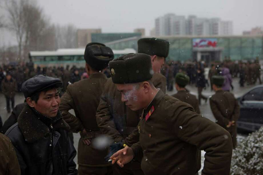 A North Korean soldier smokes a cigarette as snow falls in Pyongyang on Sunday. Photo: AP