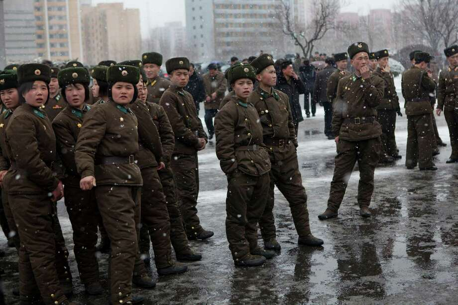 North Korean soldiers gather along a Pyongyang street during heavy snowfall on Sunday. Photo: AP