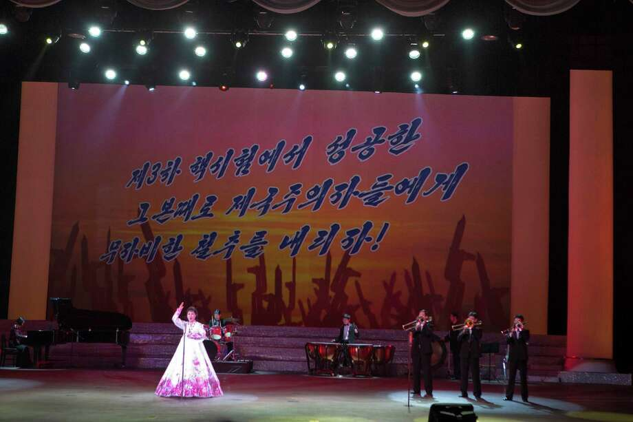 "A North Korean musical performance is held in Pyongyang with  the words ""Let's strike the imperialists mercilessly with the same success we had carrying out the 3rd nuclear test"" projected on a screen, on Sunday. Photo: AP"