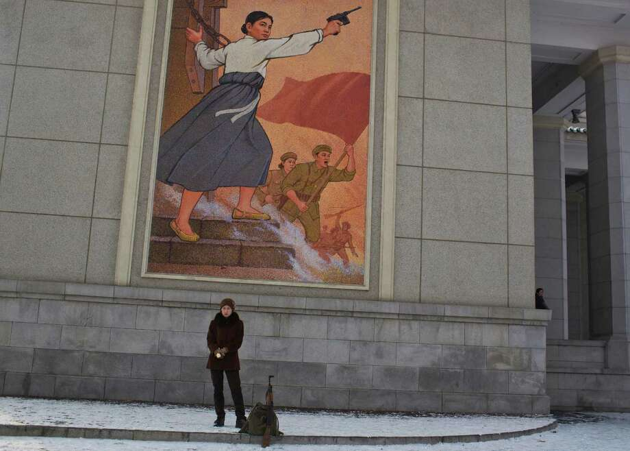 A North Korean woman, with a fake Kalashnikov rifle used in a theatrical performance, stands in front of the Pyongyang Grand Theatre waiting for a ride on Sunday. Photo: AP