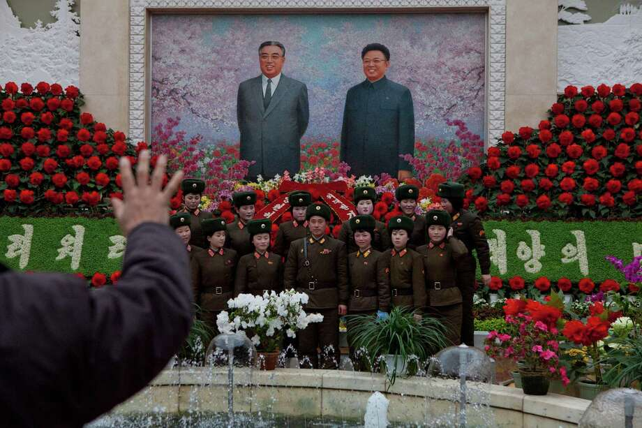 A North Korean portrait photographer instructs North Korean soldiers to pose for a picture under a mosaic of the late leaders Kim Il Sung and Kim Jong Il at an exhibition in Pyongyang on Sunday where Kimjongilia flowers, named after Kim Jong Il, were on display. Photo: AP