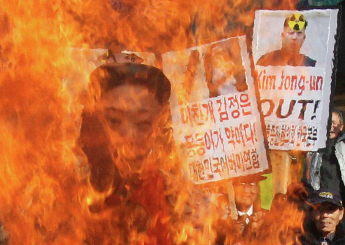 South Korean protesters burn an effigy of North Korean leader Kim Jong Un during an anti-North Korea rally denouncing the North's nuclear test in Seoul, South Korea, Wednesday. A day after North Korea defied U.N. warnings with a nuclear test, Pyongyang's neighbors turned to the business of bolstering their military preparations and sending out scientists to determine whether the detonation was as successful as the North claimed.