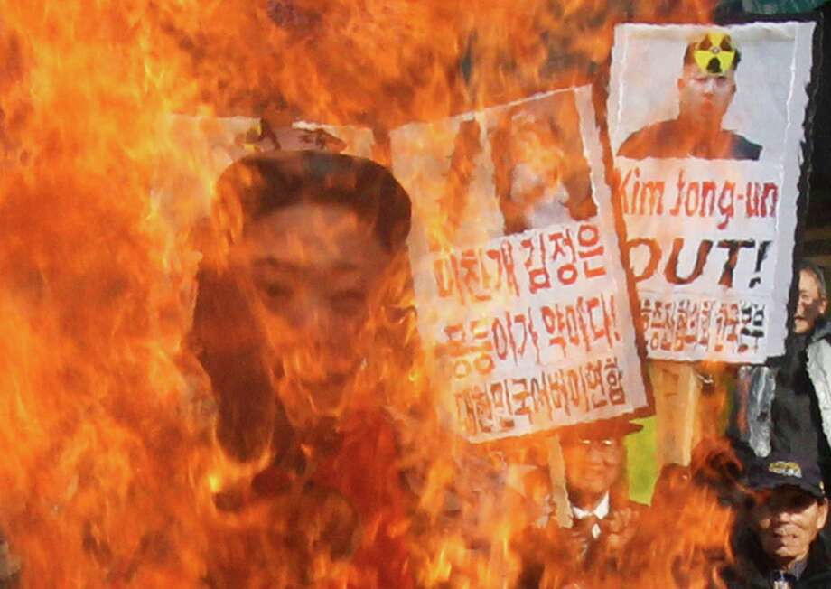 South Korean protesters burn an effigy of North Korean leader Kim Jong Un during an anti-North Korea rally denouncing the North's nuclear test  in Seoul, South Korea, Wednesday. A day after North Korea defied U.N. warnings with a nuclear test, Pyongyang's neighbors turned to the business of bolstering their military preparations and sending out scientists to determine whether the detonation was as successful as the North claimed. Photo: AP