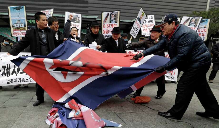 "South Korean protesters slit up a North Korean flag during an anti-North Korea rally in Seoul, South Korea, following a nuclear test conducted by North Korea Tuesday. The signs read "" Out, Kim Jong Un."" Photo: AP"