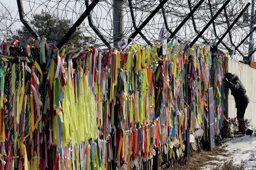 A man looks through the wire fence covered with ribbons carrying messages of people's wish for the r