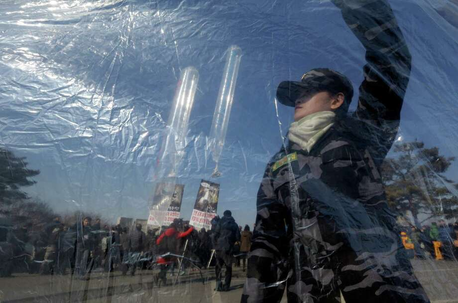 A North Korean defector prepares to release helium balloons carrying leaflets during an anti-North Korea rally denouncing North Korea's third nuclear test. Photo: AP