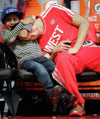 Jeremy Lin of the Houston Rockets plays with Kiyan Anthony, son of  Carmelo Anthony of the New York Knicks, after competing in the NBA All-Star Skills Challenge. Photo: Melissa Phillip, Houston Chronicle / © 2013  Houston Chronicle