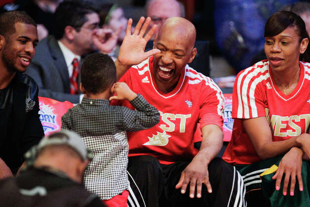 Former Houston Rockets player Sam Cassell high fives Chris Paul II, son of Chris Paul of the Los Angeles Clippers, as he sits with Tina Thompson of the Seattle Storm, right, during the NBA All-Star Shooting Stars competition. Photo: Melissa Phillip, Houston Chronicle / © 2013  Houston Chronicle