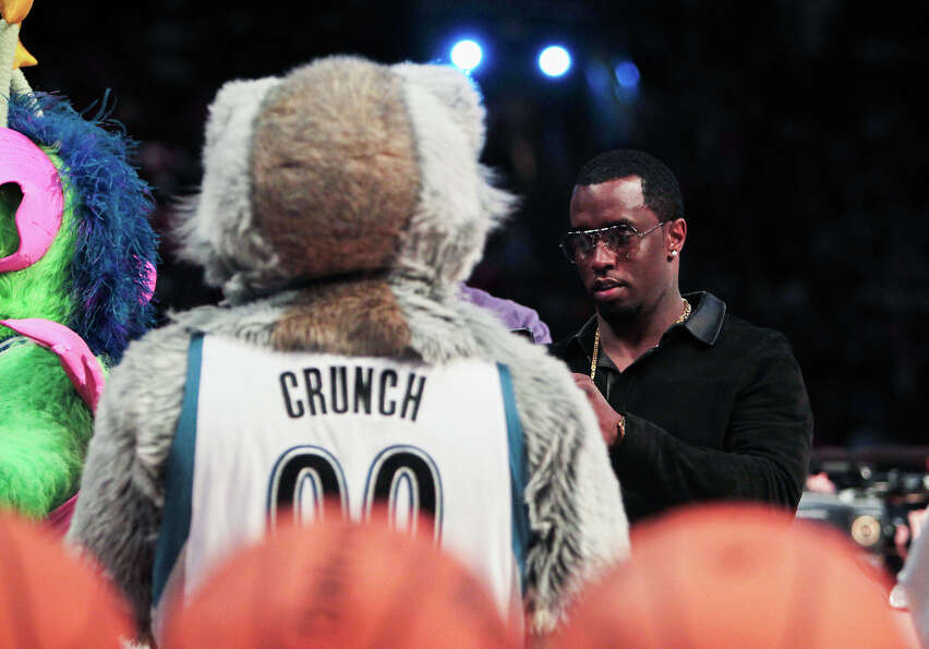 Sean Combs walks through a group of team mascots before the NBA All-Star Three-Point Contest.