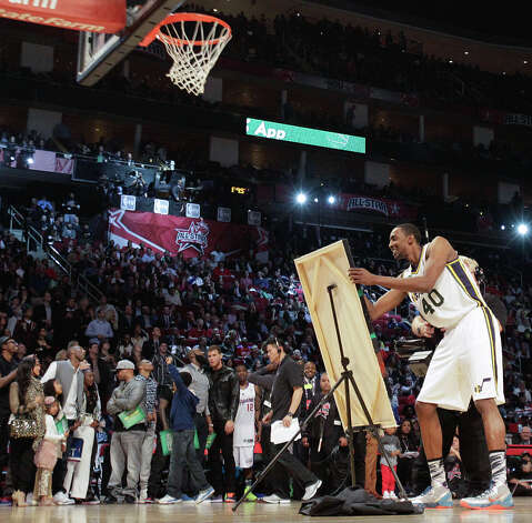 Jeremy Evans of the Utah Jazz unveils a piece of artwork after dunking during the NBA All-Star Slam Dunk Contest. Photo: Melissa Phillip, Houston Chronicle / © 2013  Houston Chronicle