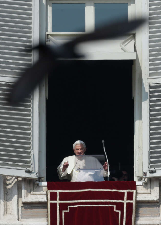 A pigeon flies in front of Pope Benedict XVI as he waves to the faithful during the Angelus noon prayer he celebrated from the window of his studio overlooking St. Peter's square, at the Vatican, Sunday. Pope Benedict XVI blessed the faithful from his window overlooking St. Peter's Square for the first time since announcing his resignation, cheered by an emotional crowd of tens of thousands of well-wishers from around the world. Photo: Alessandra Tarantino, AP / AP