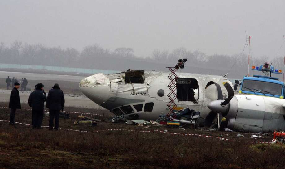 Ukrainian AN-24 plane is seen after crash outside an airport in the eastern Ukrainian city of Donetsk, Thursday. A passenger plane carrying soccer fans headed for a match between Shakhtar and Borussia Dortmund, skidded past the landing strip and overturned on Wednesday, killing five people, officials said. The plane was carrying 44 passengers and crew  from the Black Sea port of Odessa when it crash-landed. Photo: AP