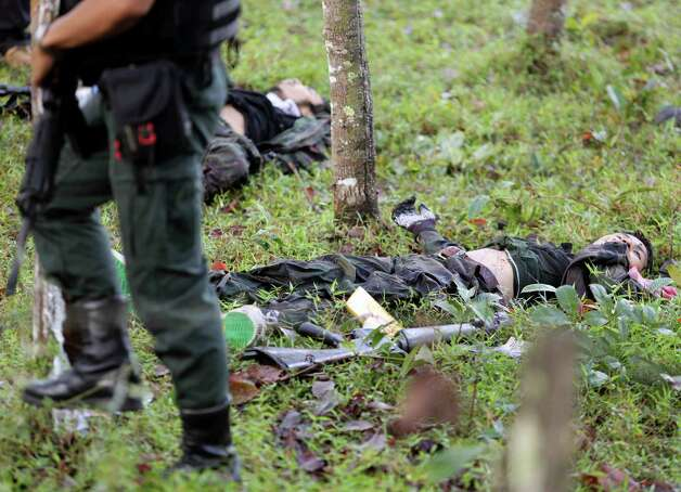 A Thai soldier walks by the dead bodies of the insurgents near a marine corps base in Narathiwat province, Thailand Wednesday, Feb. 13, 2013. Marines fending off a major militant assault on their base in Thailand's violent south killed 16 insurgents in an overnight shootout, authorities said Wednesday. It was the deadliest toll the Muslim guerrillas suffered since more than 100 died in a single day nearly a decade ago. Photo: AP