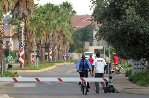 A security officer cycles towards the main gate of the housing estate where Olympian Oscar Pistorius lives, in Pretoria, South Africa, Thursday. Pistorius was charged Thursday with the murder of his girlfriend who was shot inside his home in South Africa, a stunning development in the life of a national hero known as the Blade Runner for his high-tech artificial legs. Photo: AP