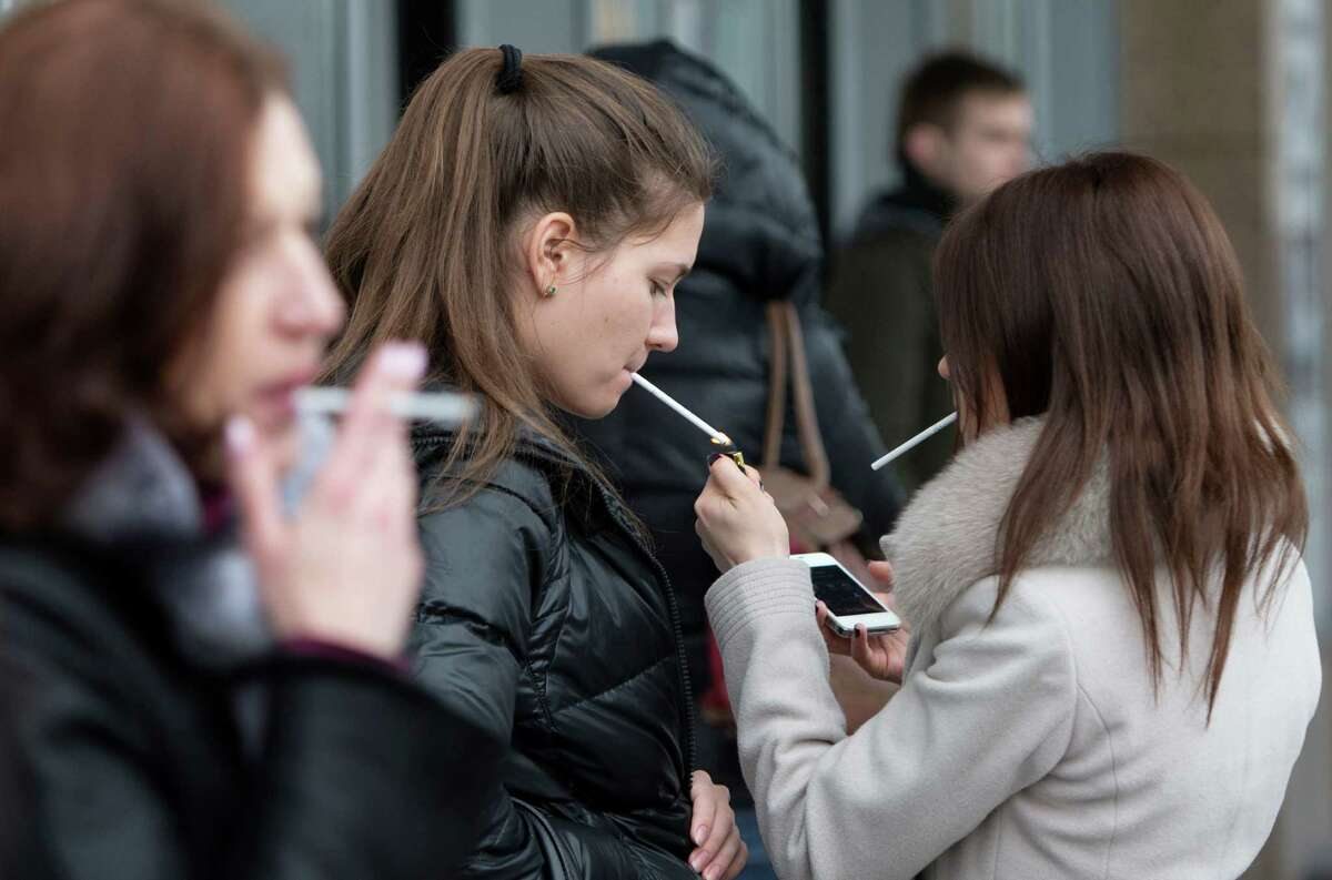 Women smoke cigarettes at a shopping center in Moscow, Russia, Tuesday. Russia's lower house of parliament has overwhelmingly passed a bill that would ban smoking in public places, a contentious measure in a country with one of the highest smoking rates in the world.