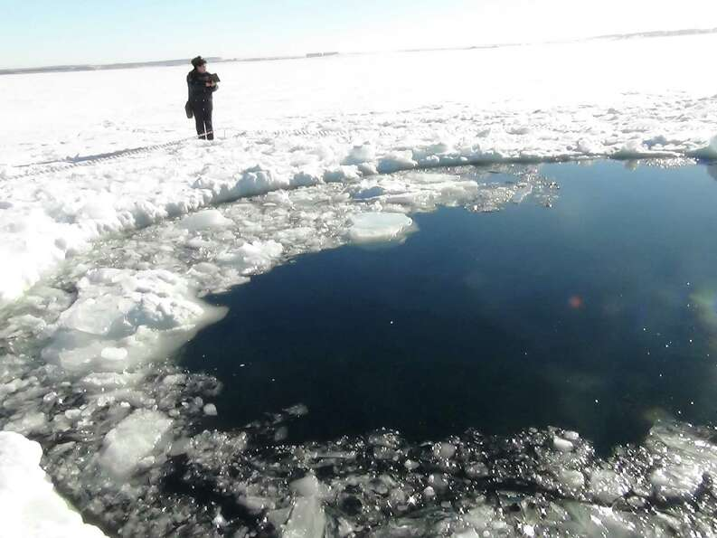 A circular hole in the ice of Chebarkul Lake where a meteor reportedly struck the lake near Chelyabi