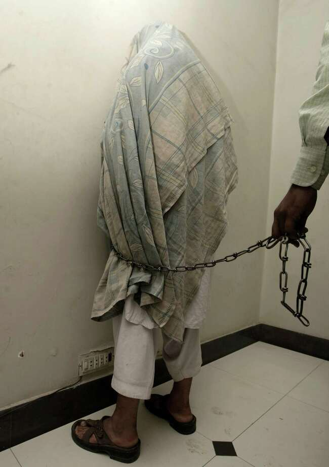 A Pakistani security official presents alleged militant Zarshad Salarzai with his face covered before the media in Karachi, Pakistan, on Wednesday. Police said he belonged to outlawed group and arrested with ammunition in a raid. He is reportedly involved in many bank robberies and drug trafficking. Photo: AP