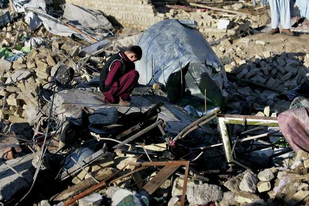 A Pakistani Shiite Muslim reacts as he sits over the rubble of a damaged market caused by Saturday's bombing in Quetta, Pakistan on Sunday. The death toll from the horrific bombing that tore through the crowded vegetable market in a mostly Shiite Muslim neighborhood of southwestern Pakistan climbed to 81 with many of the severely wounded dying overnight, a Pakistani police  official said Sunday. Photo: AP