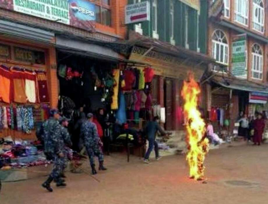 Nepalese policemen rush as a Tibetan monk burns after he set himself on fire in Katmandu, Nepal, Wednesday. The Tibetan monk doused himself with gasoline and set himself on fire in Nepal's capital Wednesday in what is believed to be the latest self-immolation to protest Chinese rule in Tibet. Nearly 100 Tibetan monks, nuns and lay people have set themselves on fire in various countries, mostly in ethnic Tibetan areas inside China, since 2009. Photo: AP