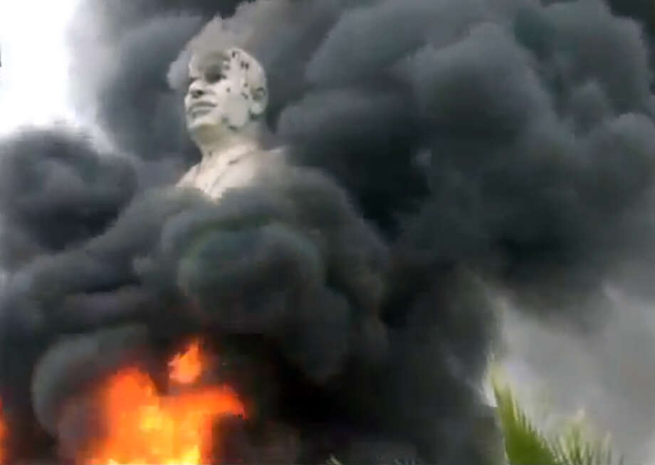 In this image taken from video obtained from Ugarit News, which has been authenticated based on its contents and other AP reporting, a statue of Hafez Assad, father of Syrian President Bashar Assad, burns after being set on fire by rebel fighters inside the grounds of the General Company of the Euphrates Dam in Al-Raqqa, Syria, Monday. Syrian rebels captured the country's largest dam on Monday after days of intense clashes, giving them control over water and electricity supplies for much of the country in a major blow to President Bashar Assad's regime. Photo: AP